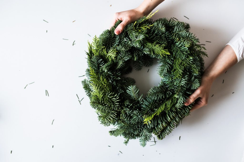 Female hands holding green Christmas wreath. Copy space.